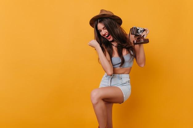 Schitterend donkerharig meisje met camera die positieve emoties uitdrukt