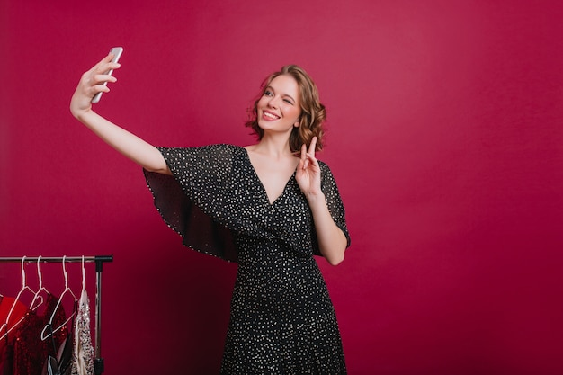 Schitterend europees meisje dat een foto van zichzelf neemt met een vredesteken in haar kamer