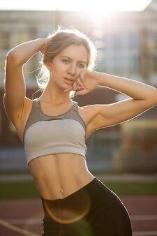 Schitterend fitnessmodel met perfect lichaam dat sportkleding draagt die zich op een tennisbaan in zonnestralen stelt