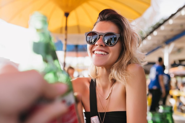 Schitterend gelooid meisje in zwarte zonnebril zomerdag doorbrengen in openluchtrestaurant. blonde vrouw lachen draagt gouden accessoires glimlachend tijdens rust in café.