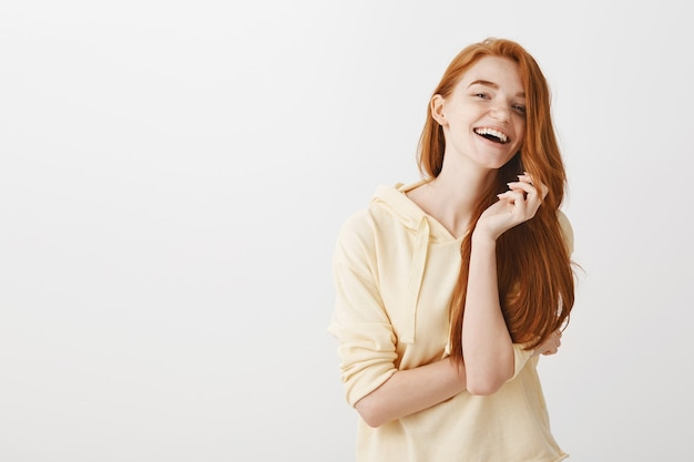 Schitterend gelukkig roodharig meisje dat zorgeloos glimlacht