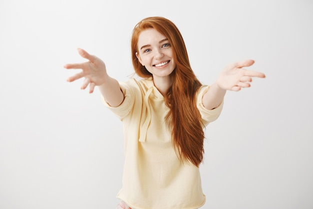 Schitterend glimlachend roodharigemeisje die handen naar voren bereiken om iets vast te houden