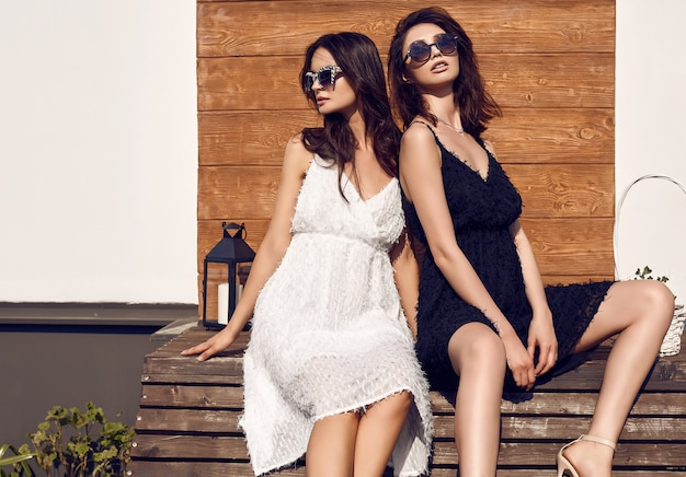 Schitterend helder paar donkerbruine vrouwen in zwart-witte jurken