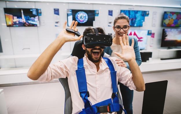 Schitterend jeugdig hipsterpaar dat pret heeft terwijl het controleren van vr in de technologieopslag.