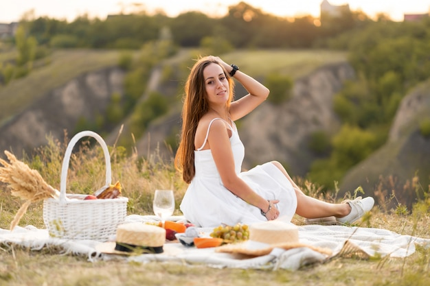 Schitterend jong donkerbruin meisje in een witte sundress die een picknick op een schilderachtige plaats heeft. romantische picknick