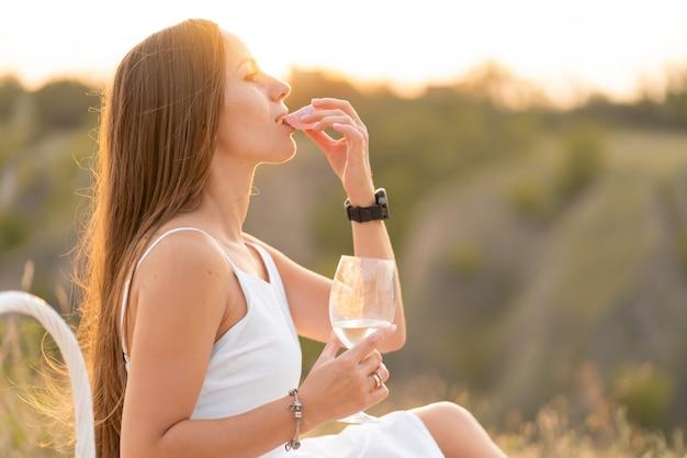 Schitterend jong donkerbruin meisje in een witte zomerjurk die van een picknick op een schilderachtige plaats genieten. romantische picknick