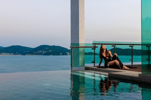 Schitterend jong meisje in een lange zwarte jurk zit met een glas champagne in de buurt van het overloopzwembad, prachtig uitzicht op de zee