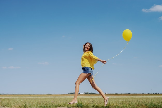 Schitterend kaukasisch tienermeisje in gele blouse, denim shorts en met een bril die buiten loopt met een gele ballon in de hand.