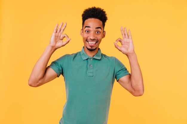 Schitterend mannelijk model in het groene t-shirt stellen met goed teken. binnen schot van zalige afrikaanse man positieve emoties uitdrukken.