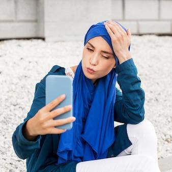 Schitterend meisje dat buiten een selfie neemt