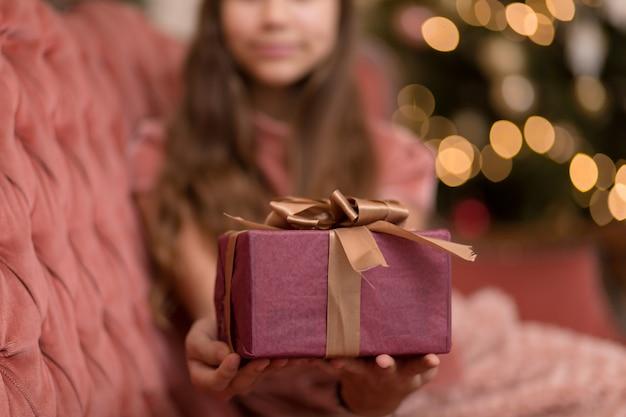 Schitterend meisje met een kerstcadeautje in een stijlvol interieur.