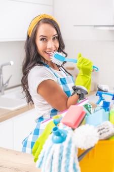 Schitterend meisje met gele hoofdband, rubberen handschoenen en een blauw-wit geblokte schort die in een keukenborstel zingt in plaats van huishoudelijk werk te doen met een emmer vol schoonmaakspullen voorin.