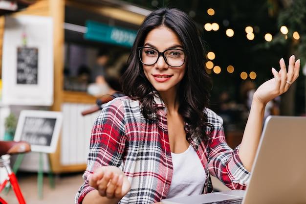 Schitterend meisje met golvend haar met behulp van computer en glimlachen. openluchtportret van kaukasische dame die belangstelling uiten tijdens het werk met laptop.