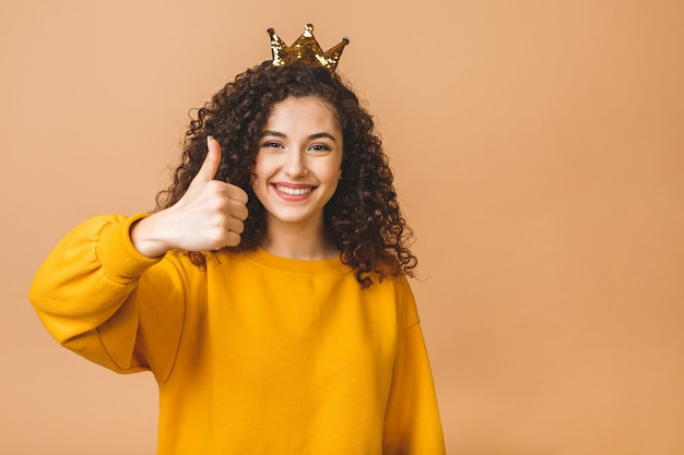 Schitterend mooi meisje met krullend bruin haar en casual dragen en kroon op hoofd houden die over beige studioachtergrond wordt geïsoleerd. duimen omhoog.