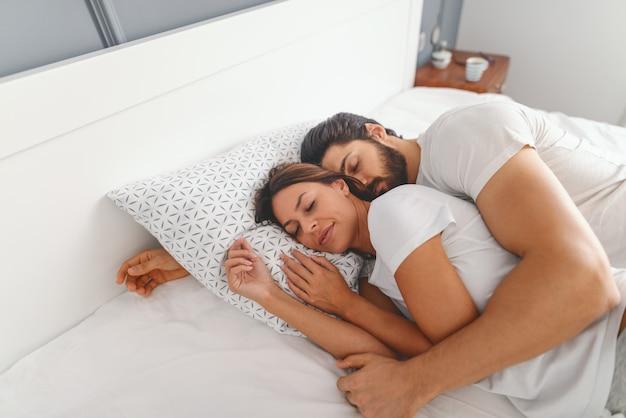 Schitterend paar dat in slaapkamer slaapt. man knuffelen zijn liefhebbende vrouw. ochtend tijd.