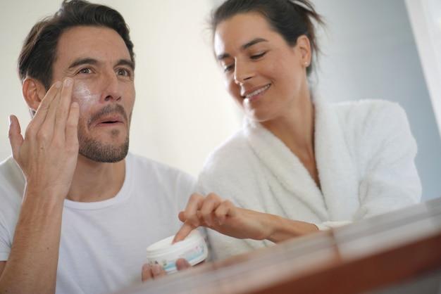 Schitterend paar die door dagelijks schoonheidsregime in badkamers gaan