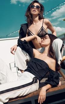 Schitterend paar donkerbruine vrouwen in manierkleding die op het dak stellen