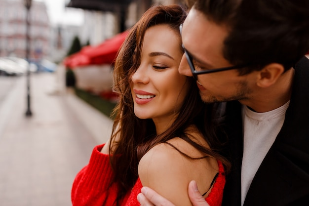 Schitterend paar verliefd knuffelen en flirten buiten. romantische momenten. knappe man kijkt op zijn mooie vriendin.