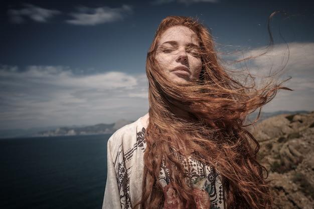Schitterend romantisch meisje buitenshuis. mooi model dichtbij zee. lang haar waait in de wind. roodharig meisje in etnisch kostuum aan de oceaankust