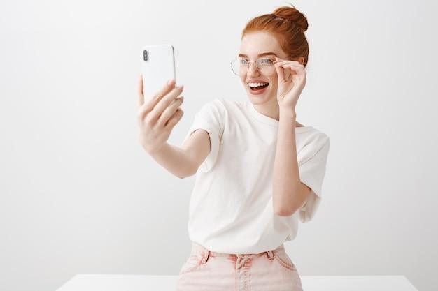 Schitterend roodharig meisje dat selfie met bril neemt