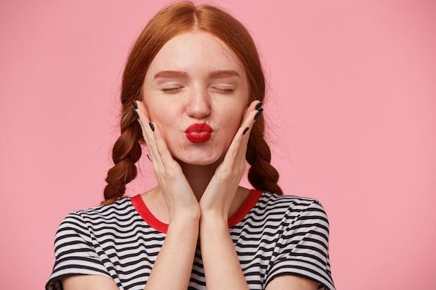 Schitterend roodharig meisje met twee vlechten die haar gezicht met handpalmen vasthouden en luchtkus met rode lippen, ogen gesloten, geïsoleerd stuurt