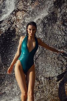 Schitterend slank meisje in oorbellen met nat haar in een modieus zwempak tegen de achtergrond van een waterval