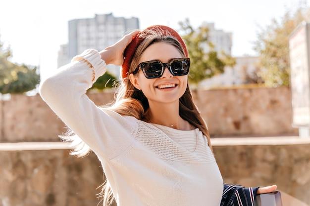 Schitterend stijlvol meisje uiting van geluk in herfstdag. buitenfoto van prachtige witte dame in rode baret.