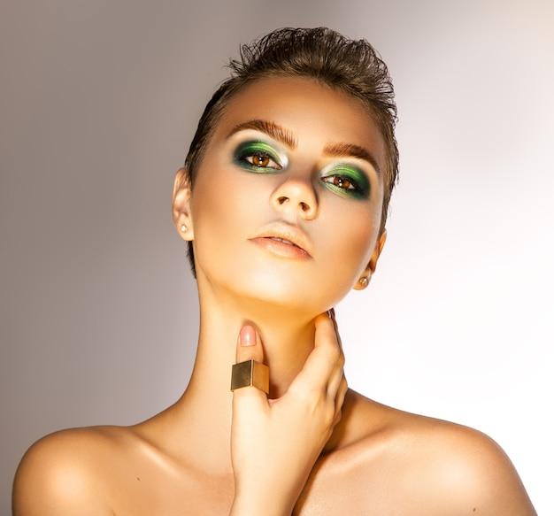 Schitterend volwassen meisje met mooie groene kleuren make-up in studio camera kijken