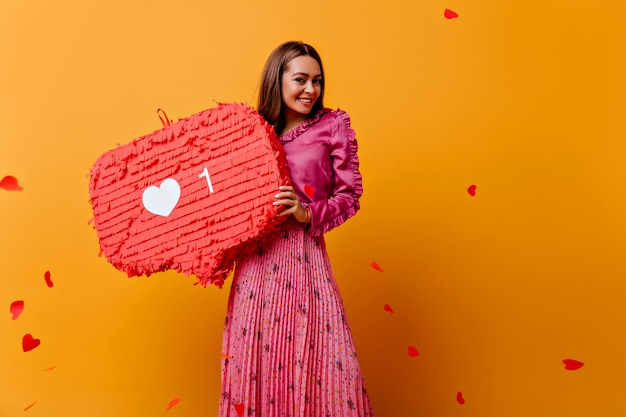 Schitterend, vrolijk, vrolijk meisje poseren met rode versieringen in haar handen. portret van bruinharige vrouw in roze outfit tegen muur van confetti in vorm van harten