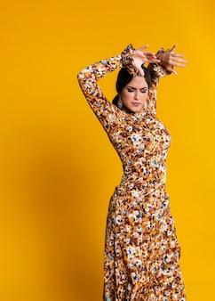 Schitterend vrouw het dansen flamenco met oranje achtergrond