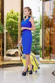 Schitterende aantrekkelijke jonge aziatische vrouw die met een kleine koffer chique hotel verlaat