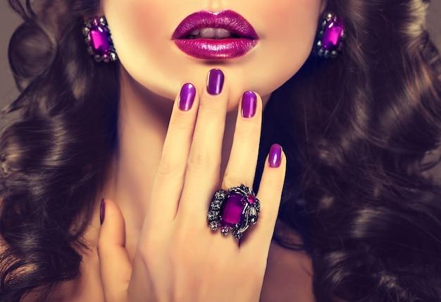 Schitterende avondmake-up en sieraden in paarse tinten. sierlijke vingers, versierd met een grote ring en nauwkeurige violette manicure, voor de goed gevormde lippen in paars gekleurd.