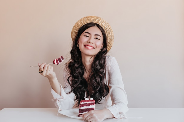 Schitterende aziatische vrouw die cake eet. glimlachende verjaardagsvrouw die van dessert geniet.
