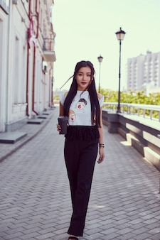 Schitterende aziatische vrouw die in manierkleding langs heldere straat loopt