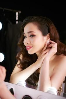 Schitterende aziatische vrouw die op een mooie oorring zet die in de spiegel kijkt