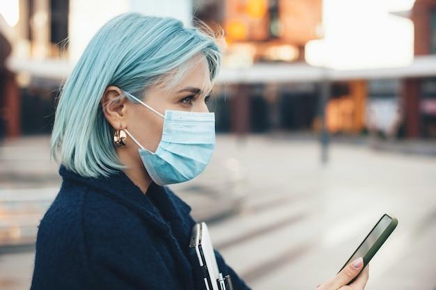 Schitterende blanke ondernemer met blauw haar poseren met moderne gadgets terwijl ze een anti-griepmasker draagt