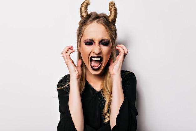 Schitterende blanke vrouw in vampierkostuum die op witte muur gillen. trendy meisje in zwarte kleding die op halloween-fotoshoot voor de gek houdt.