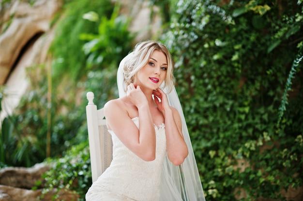 Schitterende blonde bruidzitting op stoel en gesteld bij grote geweldige huwelijkszaal