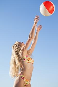Schitterende blonde in bloemenbikini die strandbal werpt