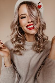 Schitterende blonde vrouw in bruine trui die naar voren glimlacht