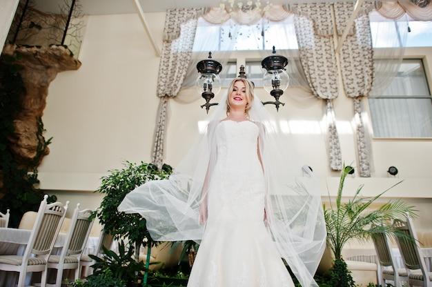 Schitterende blondebruid met lange sluier die bij grote ontzagwekkende huwelijkszaal lantaarn wordt gesteld als achtergrond