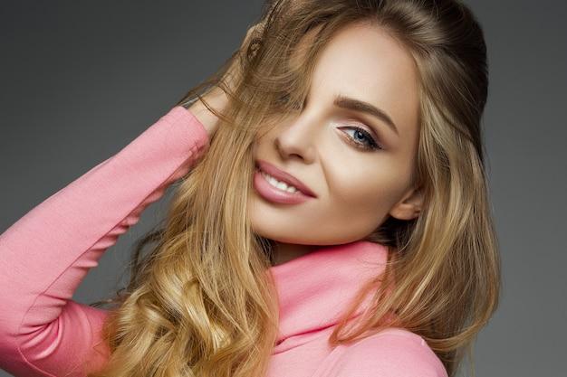 Schitterende blondevrouwensualiteit die bij camera glimlachen.