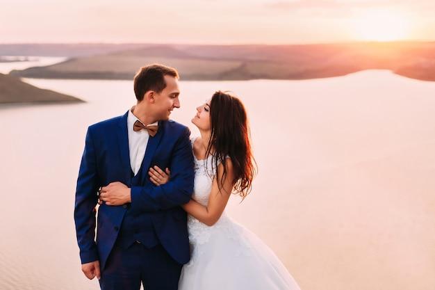 Schitterende bruid die bruidegom van erachter koestert en hem bekijkt