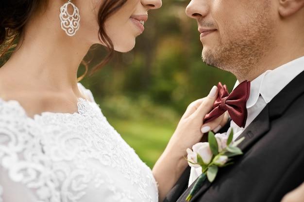 Schitterende bruid die een rode vlinderdas van modieuze bruidegom aanpast tijdens de huwelijksceremonie