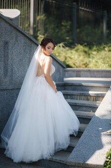 Schitterende bruid in elegante jurk buitenshuis.