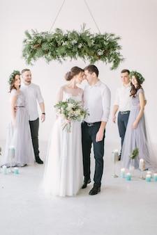 Schitterende bruid met pioen boeket en stijlvolle bruidegom poseren met bruidsmeisjes en groomsman op trouwdag