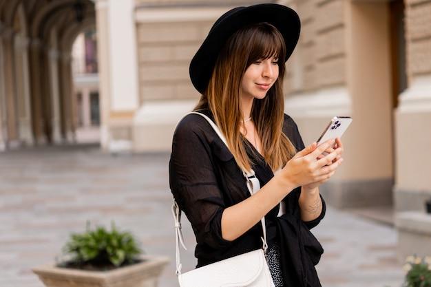 Schitterende bruneete vrouw in stijlvolle herfstoutfit en achterhoed die met een mobiele telefoon op straat in de oude europese stad praat