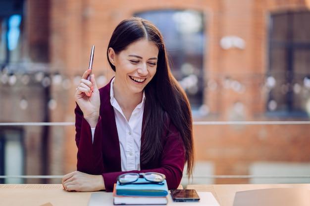 Schitterende brunette die breed glimlachend een pen houdt herinnerend pretverhaal na vergadering terwijl het zitten aan de lijst met agenda, glazen en smartphone op het. business en management.