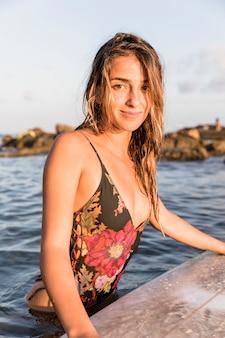 Schitterende dame die zich dichtbij surfplank in overzees bevindt