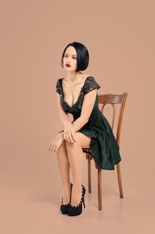 Schitterende dame in korte kledingszitting op stoel in studio met beige achtergrond